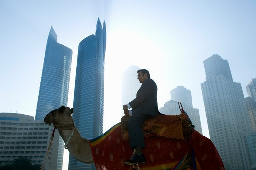 Stock Photo: 4304R-4815 Businessman sitting on camel, towers seen through the mist in the background