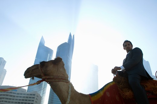 Businessman sitting on camel, towers seen through the mist in the background : Stock Photo