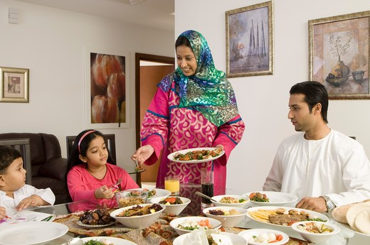 Mother serving food to family : Stock Photo