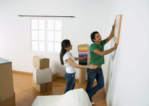 Young couple deciding position to hang painting : Stock Photo