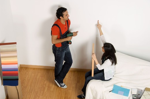 Stock Photo: 4304R-5003 Young couple deciding position to hang painting