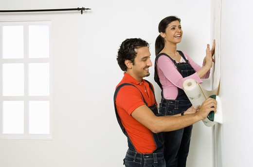 Stock Photo: 4304R-5010 Young couple fixing wall paper