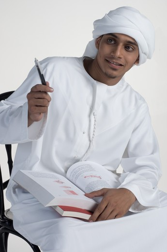 Young man writing, smiling : Stock Photo