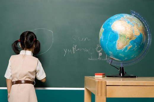 Stock Photo: 4304R-5567 Girl (6-7) drawing on blackboard, rear view