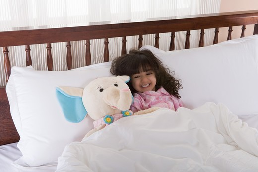 Stock Photo: 4304R-6049 Girl (3-4) lying on bed by toy, smiling