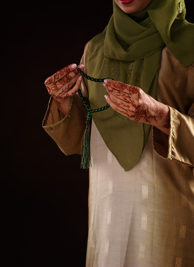 Young woman holding prayer beads, close-up : Stock Photo
