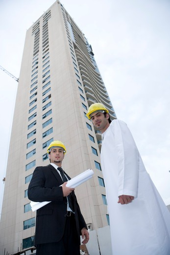 Businessmen standing with blueprints by building, low angle view, portrait : Stock Photo