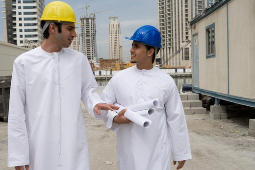 Businessmen in Dishdash at construction site with layouts : Stock Photo