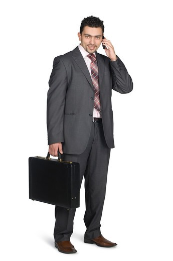 Stock Photo: 4304R-6192 Businessman holding mobile phone and briefcase, portrait