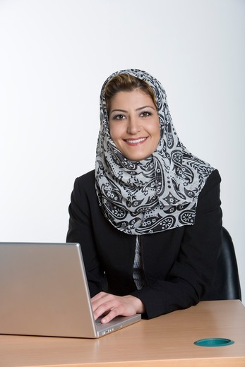 Stock Photo: 4304R-6414 Young woman using laptop, smiling, portrait