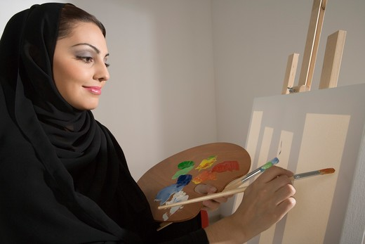 Stock Photo: 4304R-6497 Young woman holding palette, painting, side view