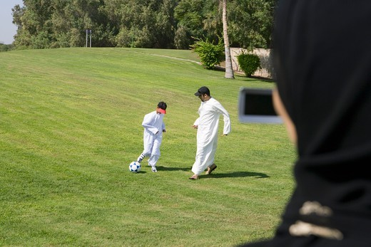 Father and son playing football at park while woman taking photograph : Stock Photo