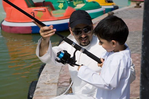 Father with son holding fishing rod, smiling, : Stock Photo