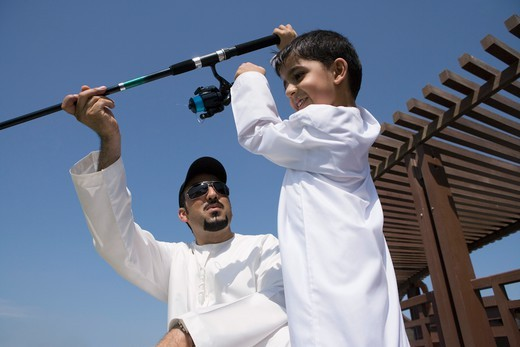 Stock Photo: 4304R-6592 Father with son holding fishing rod