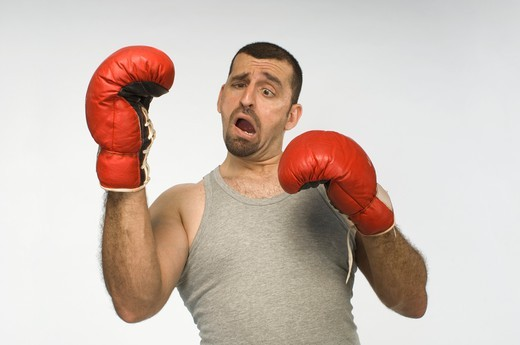 Mid adult man with red boxing gloves against white background : Stock Photo