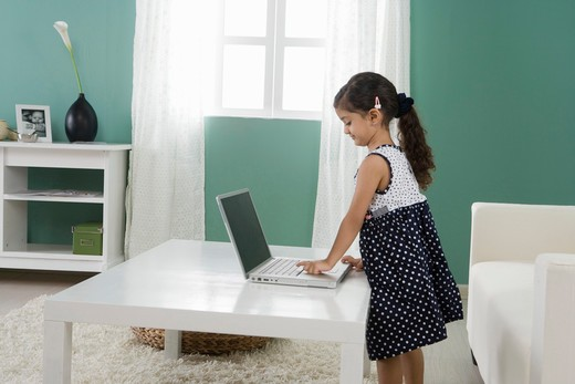 Stock Photo: 4304R-6880 Girl (4-5 years old) using laptop at home