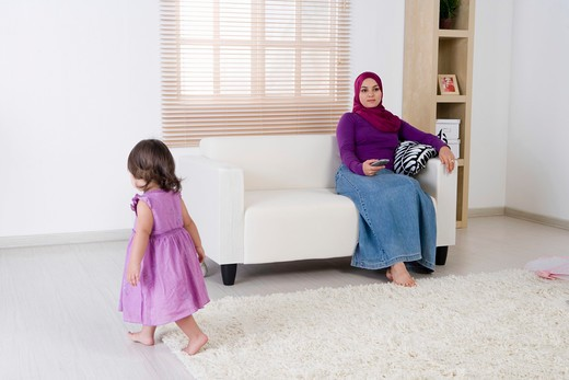 Stock Photo: 4304R-6912 Mother holding the television remote control, daughter walking around
