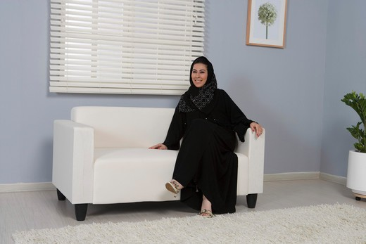 Arab woman sitting on a sofa, smiling : Stock Photo