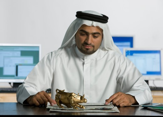 Stock Photo: 4304R-7016 Arab man looking at the bull figurine on top of the table