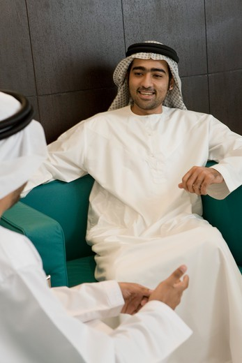 Two Arab businessmen sitting in office, discussing, smiling : Stock Photo