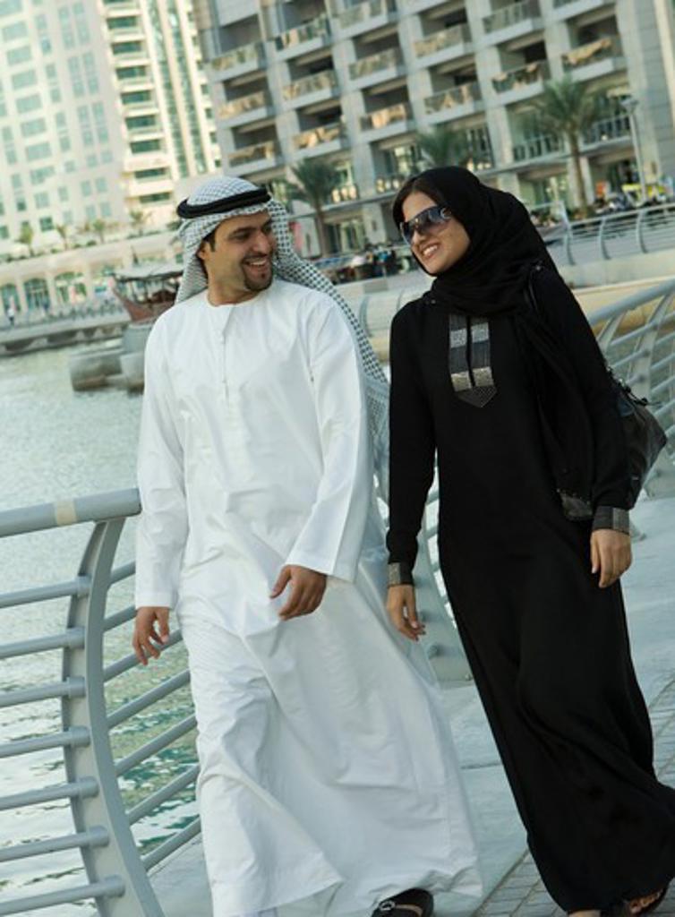 Stock Photo: 4304R-7128 Arab couple walking at Dubai Marina, UAE