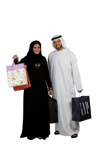 Arab couple with shopping bags, smiling : Stock Photo