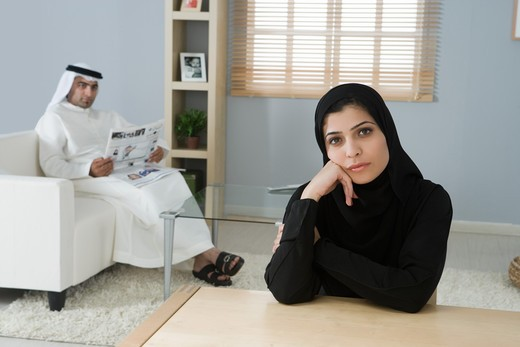 Arab couple in the living room, woman looking at the camera : Stock Photo