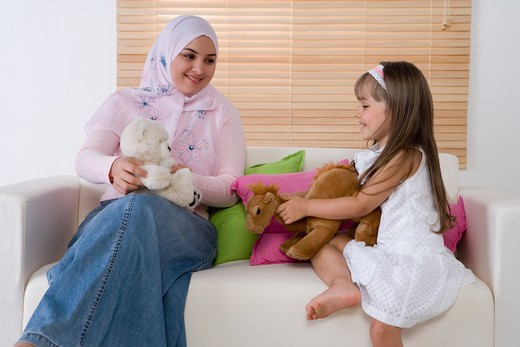 Mother and daughter sitting on sofa, playing with toys : Stock Photo