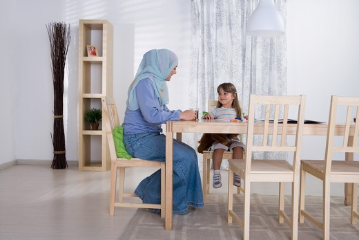 Arab mother helping her daughter with homework : Stock Photo