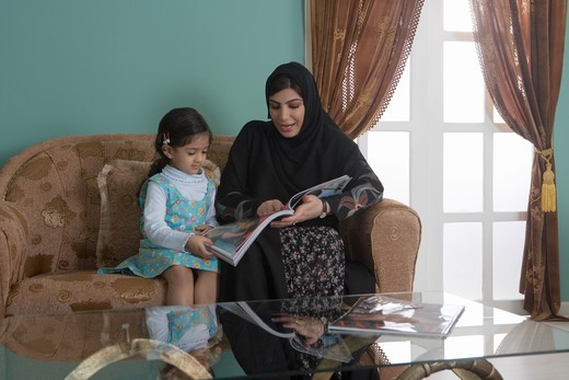 Stock Photo: 4304R-7564 Arab mother and daughter reading magazine, sitting in the sofa