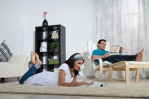 Stock Photo: 4304R-7673 Couple reading in the living room