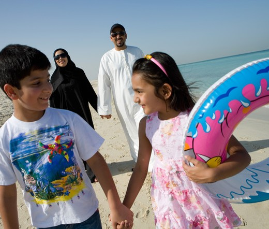 Family walking on beach, smiling : Stock Photo