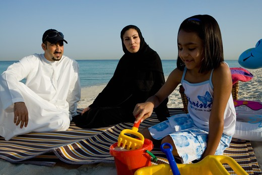Family sitting on beach, smiling : Stock Photo