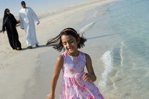 Girl running on beach while parent walking behind : Stock Photo
