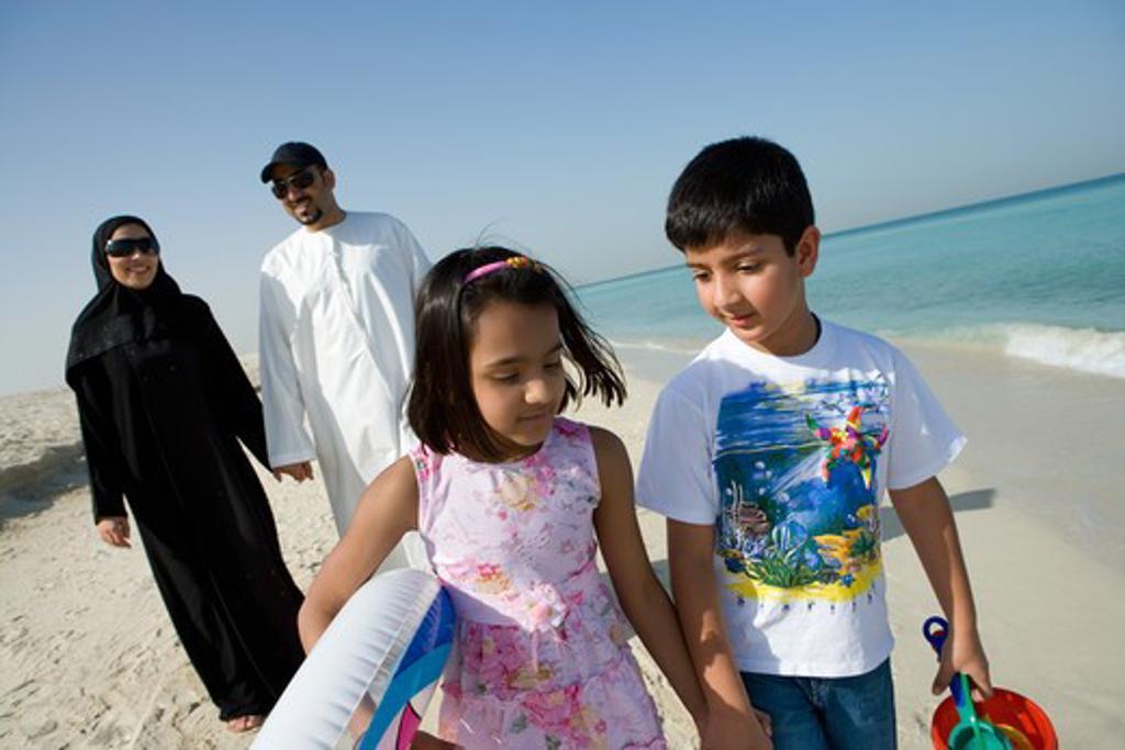 Stock Photo: 4304R-8185 Family walking on beach, smiling