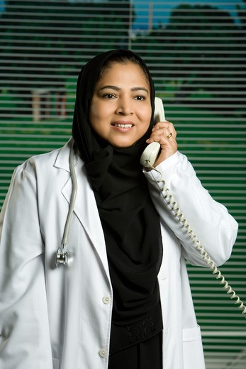 Stock Photo: 4304R-8214 Female doctor talking on telephone, smiling, portrait.