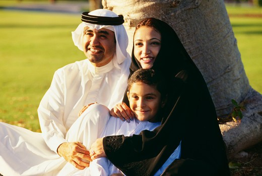An Arabian family shares a light moment as they sit under the tree and smile. : Stock Photo