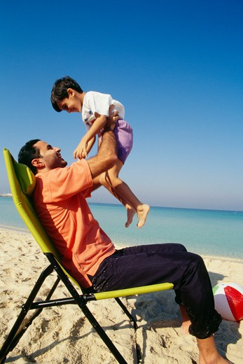 A father holds his son while seated on the chair as they enjoy at the beach. : Stock Photo