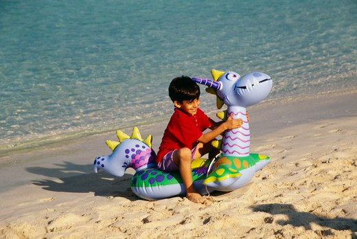 Stock Photo: 4304R-8414 A small boy sits on an air filled toy as he enjoys at the beach.