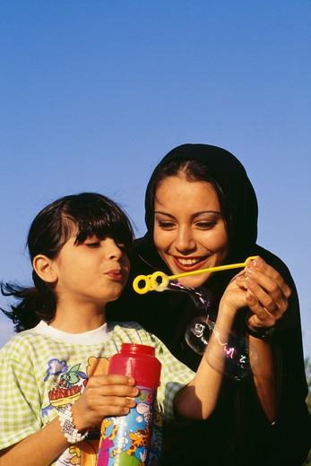 A girl blows off the soap bubble while the mother holds her hand. : Stock Photo