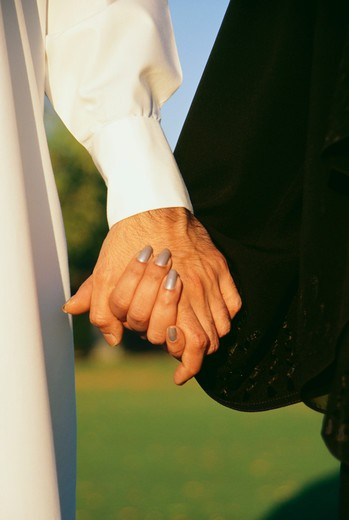 A couple clasping each others hand is seen at close up. : Stock Photo