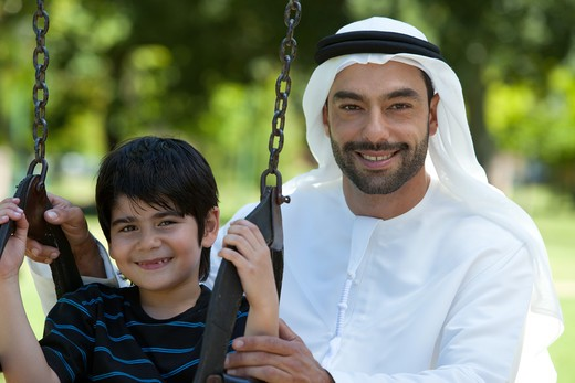 Stock Photo: 4305R-1080 Portrait of an arab father and son at the park, boy sitting on swing.