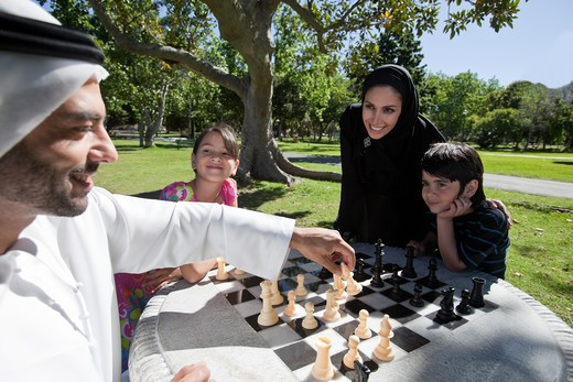 Stock Photo: 4305R-1094 Arab family playing chess together at the park.