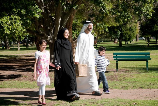Arab family with picnic basket holding hands while walking at the park. : Stock Photo