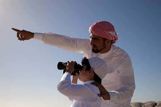 Stock Photo: 4305R-1150 Arab father and son looking through binoculars by the beach.