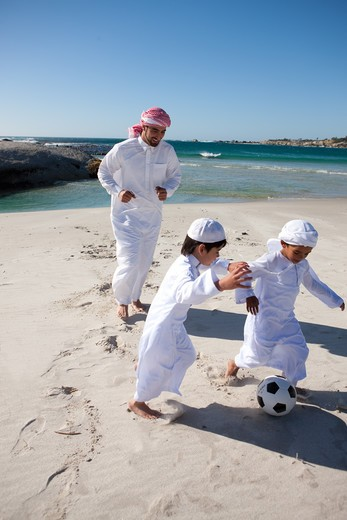 Stock Photo: 4305R-1155 Arab father with two sons playing soccer ball by the beach.