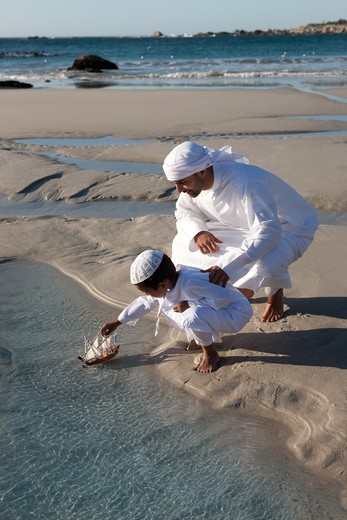 Stock Photo: 4305R-1179 Arab father and son playing toy boat on beach.