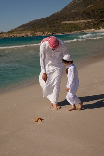 Stock Photo: 4305R-1189 Arab father and son looking at a starfish on the beach.