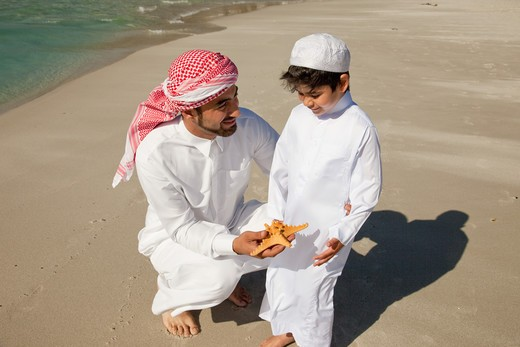 Arab father and son with starfish at the beach. : Stock Photo