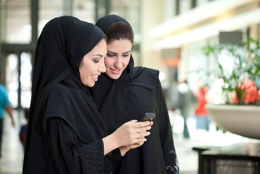 Stock Photo  4305R-1238 Two young arab women using mobile phone at the  shopping 02152c6c0e